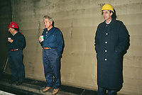 Switzerland. Canton Lucerne. Three bored men in the Sonnenberg tunnel in Lucerne during the largest civil defense exercise ever held in the country. From 16 to 21 November 1987, almost 1200 men and women converted a motorway tunnel into perhaps the world's largest bunker structure. The civil protectors had to prove during the exercise «Ameise» ( Ants in english) that in an emergency more than 20,000 inhabitants of the city of Lucerne could survive here in the mountain for two weeks. The Sonnenberg Tunnel is a 1,550m  long motorway tunnel, constructed between 1971 and 1976. At its completion it was also the world's largest civilian nuclear fallout shelter, designed to protect 20,000 civilians in the eventuality of war or disaster. Based on a federal law from 1963, Switzerland aims to provide nuclear fallout shelters for the entire population of the country. The construction of a new tunnel near an urban centre was seen as an opportunity to provide shelter space for a large number of people at the same time. The giant bunker was built between 1970 and 1976 at a cost of 40 million Swiss francs. The shelter consisted of the two motorway tunnels (one per direction of travel), each capable of holding 10,000 people in 64 person subdivisions. A seven story cavern between the tunnels contained shelter infrastructure including a command post, an emergency hospital, a radio studio, a telephone centre, prison cells and ventilation machines. The shelter was designed to withstand the blast from a 1 megaton nuclear explosion 1 kilometer away. The blast doors at the tunnel portals are 1.5 meters thick and weigh 350 tons. The logistical problems of maintaining a population of 20,000 in close confines were not thoroughly explored, and testing the installation was difficult because it required closing the motorway and rerouting the usual traffic. The only large-scale test, a five-day exercise in 1987 to practice converting the road tunnels into usable shelters, revealed many pro