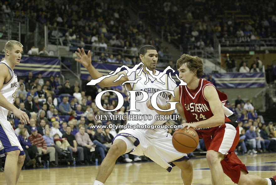 05 Dec 2004:Eastern Eagles forward Paul Butorac races past Washington Husky Tre Simmons as he goes up for a bucket against the in Seattle, WA...