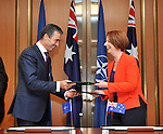 Secretary General of NATO Anders Rasmussen L and Australian Prime Minister Julia Gillard R exchange documents after signing a joint decleration between Australia and NATO  at Parliament House Canberra, on Thursday June 14th 2012. AFP PHOTO / Mark GRAHAM