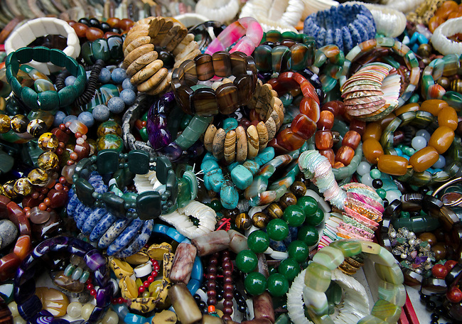 Hong Kong urban scene street market jewelry piled on table for sale - jade, stone