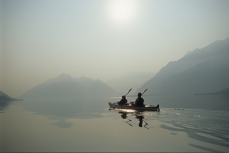 Sea kayakers paddle the calm water of Harriman Fjord in the Gulf of Alaska, north of Whittier, Alaska, in air filled with smoke from forest wildfires burning far away in the state's interior. Air quality can suffer hundreds of miles from a fire.