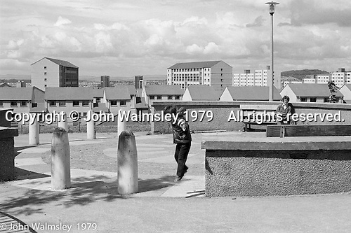 A dad watches his son jumping, Wester Hailes, Scotland, 1979.  John Walmsley was Photographer in Residence at the Education Centre for three weeks in 1979.  The Education Centre was, at the time, Scotland's largest purpose built community High School open all day every day for all ages from primary to adults.  The town of Wester Hailes, a few miles to the south west of Edinburgh, was built in the early 1970s mostly of blocks of flats and high rises.