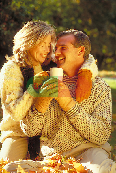 smiling couple sharing drink outdoors in autumn