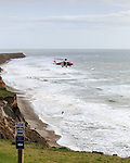A coastguard helicopter performs a sea rescue along the cliffs at Compton Bay on the Isle of Wight