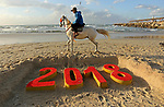 A Palestinian man rides his horse past a 2018 sand writing at a beach in Gaza City on December 31, 2017 on the last day of the year. Photo by Ashraf Amra