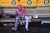 "OAKLAND, CA - AUGUST 26:  Robinson Chirinos #61 of the Texas Rangers gets ready in the dugout before the game against the Oakland Athletics at the Oakland Coliseum on Saturday, August 26, 2017 in Oakland, California. Note: both teams are wearing special colorful uniforms for ""Players Weekend"" that also include nicknames on the backs of their jerseys. (Photo by Brad Mangin)"