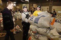 Wednesday, February 13, 2013.  Volunteers (L to R) Elder Brad Greer, Wendy Walters and Elder Aaron Nelson, stack musher's food drop bags at Airland Transport in Anchorage to be sent out to the 22 checkpoints along the trail..Iditarod 2013