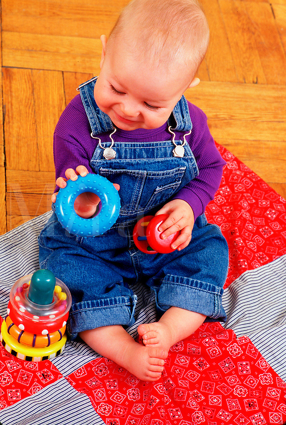 A toddler boy plays on the floor looking at a toy