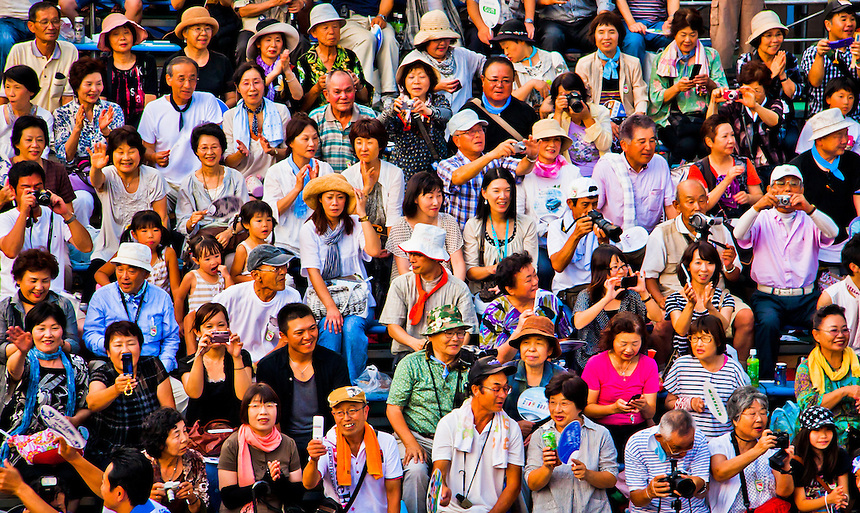 Crowd of Japanese with various cameras snap away at an event.