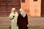 North Africa, Africa, Morocco, Marrakesh. Two Morrocan women in traditional dress converse on a street of Marrakesh.