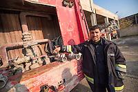 Feuerwehr in Qamishli, Rojava/Syrien.<br /> Von sieben Feuerwehr-Fahrzeugen die der YPG-Regierung in Qamishli zur Verfuegung stehen, ist nur eines funktionstuechtigt. Fuenf Fahrzeuge sind mit vorhandenen Mitteln nicht zu reparieren - Motorschaden, unbenutzbare Fahrerkabinen, defekte Stromleitungen.<br /> Zusaetzlich zumden Augaben der Feuerwehr muessen die 12 Feuerwehrmaenner - je 3 von ihnen arbeiten in 24-Stundenschichten - auch noch Wasser in Stadtteile ohne Wasserversorgung verteilen.<br /> Im Bild: Der arabische Feuerwehrmann Aziz an einem kaputten Feuerwehrfahrzeug. An diesem sind die Wasserpumpen defekt.<br /> 15.12.2014, Qamishli/Rojava/Syrien<br /> Copyright: Christian-Ditsch.de<br /> [Inhaltsveraendernde Manipulation des Fotos nur nach ausdruecklicher Genehmigung des Fotografen. Vereinbarungen ueber Abtretung von Persoenlichkeitsrechten/Model Release der abgebildeten Person/Personen liegen nicht vor. NO MODEL RELEASE! Nur fuer Redaktionelle Zwecke. Don't publish without copyright Christian-Ditsch.de, Veroeffentlichung nur mit Fotografennennung, sowie gegen Honorar, MwSt. und Beleg. Konto: I N G - D i B a, IBAN DE58500105175400192269, BIC INGDDEFFXXX, Kontakt: post@christian-ditsch.de<br /> Bei der Bearbeitung der Dateiinformationen darf die Urheberkennzeichnung in den EXIF- und  IPTC-Daten nicht entfernt werden, diese sind in digitalen Medien nach §95c UrhG rechtlich geschuetzt. Der Urhebervermerk wird gemaess §13 UrhG verlangt.]
