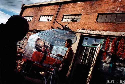Tieling city, Liaoning Province, China, 11-2003..Laid-off factory workers in China's northeastern rustbelt find new livelihood with a tricycle. The couple used to work in the factory behind them. Millions of workers are made unemployed as China restructures its economy, slashing the bloated state-sector economy and closing factories..