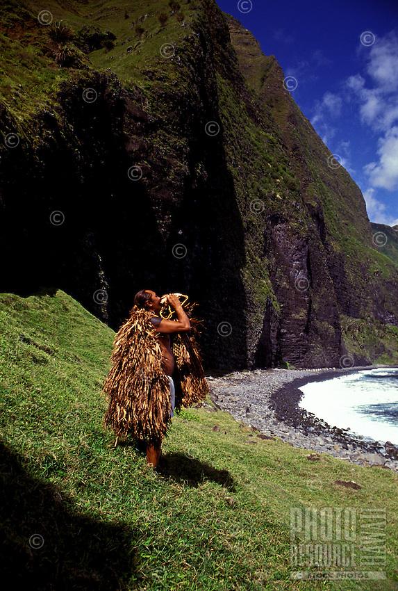 Man wearing traditional Hawaiian raincoat blowing conch shell at the mouth of Waikolu Valley, on the island of Molokai, Hawaii.