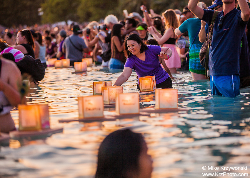 Asian woman placing lantern into the water during the 15th Annual Lantern Floating Ceremony at Ala Moana Beach Park in Honolulu on Memorial Day