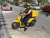 Spanish postman on a yellow scooter delivers mail in San Pedro de Alcantara, Malaga Province, Spain, 18th March 2019, 201903181218<br /><br />Copyright Image from Victor Patterson, 54 Dorchester Park, <br />Belfast, UK, BT9 6RJ<br /><br />t1: +44 28 9066 1296 (from Rep of Ireland 048 9066 1296)<br />m: +44 7802 353836<br />e: victorpattersonbelfast@gmail.com<br />w: www,victorpatterson.com<br /><br />Please see my Terms and Conditions of Use at https://www.victorpatterson.com/page2<br />It is IMPORTANT that you familiarise yourself with them.<br /><br />Images used on the Internet incur an additional cost and must be visibly watermarked i.e. © Victor Patterson within the body of the image and copyright metadata must not be deleted. Images used on the Internet have a size restriction of 4kbs and are chargeable at rates available at victorpatterson.com.<br /><br />This image is only available for the use of the download recipient i.e. television station, newspaper, magazine, book publisher, etc, and must not be passed on to any third party. It is also downloaded on condition that each and every usage is notified within 7 days to victorpattersonbelfast@gmail.com.<br /><br />The right of Victor Patterson to be identified as the author is asserted in accordance with The Copyright Designs And Patents Act (1988). All moral rights are asserted.