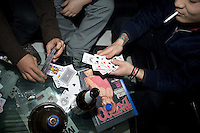 Punk musicians smoke marijuana, drink beer, and play cards late at night in a tattoo parlor in Nanjing, China.