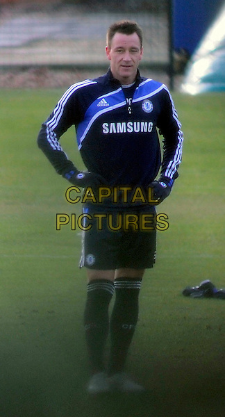 JOHN TERRY.Training at the Chelsea Football Training grounds, Cobham, Surrey, England..February 1st, 2010.full length footballer sport soccer uniform kit black blue shorts top hands on hips gloves socks.CAP/MUR.©Murphy/Capital Pictures