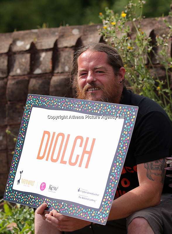 Pictured: A man with a Diolch sign by the mythical beast sculpture by artist Gwen Heeney Saturday 13 August 2016<br /> Re: Grow Wild event at  Furnace to Flowers site in Ebbw Vale, Wales, UK