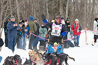 Jessie Royer and team run past spectators on the bike/ski trail near University Lake with an Iditarider in the basket and a handler during the Anchorage, Alaska ceremonial start on Saturday, March 7 during the 2020 Iditarod race. Photo © 2020 by Ed Bennett/Bennett Images LLC
