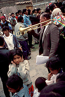 A girl holds her ears as the trombone player above her blasts a tune in Ollantaytambo. The crowd had gathered for processions and festivities for the Feast of the Pentecost.