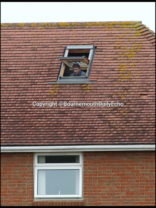BNPS.co.uk (01202 558833)<br /> Pic: RichardCrease/BNPS<br /> <br /> Poole Town v Cambridge City in the Southern Premier league this weekend. <br /> <br /> Enterprising home boss Tommy Killick watches the game from the attic window of his groundsman's house, after receiving a 6 match ban from the dugout.