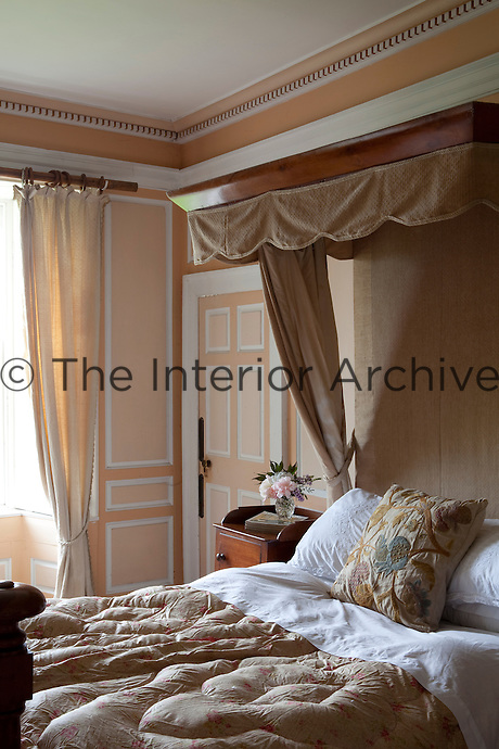 A wooden half-tester gives stature to a double bed in this peach-colour panelled bedroom