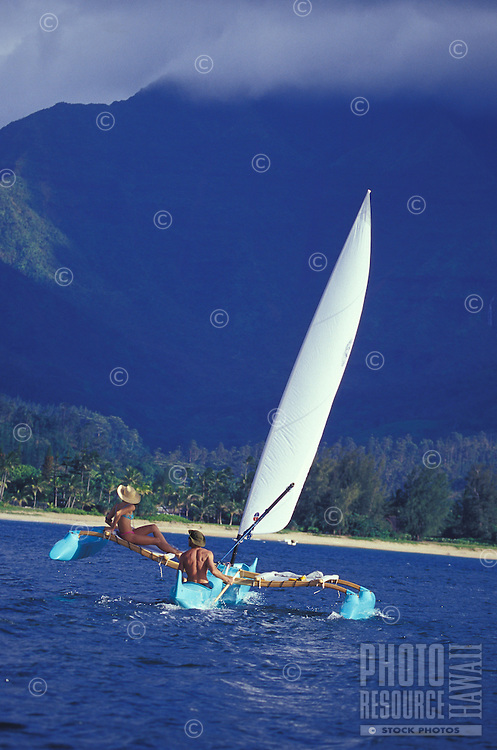 Couple sailing Hawaiian 'holopuni' outrigger canoe in tradewinds with Mount Waialeale in background, on Hanalei Bay, Kauai
