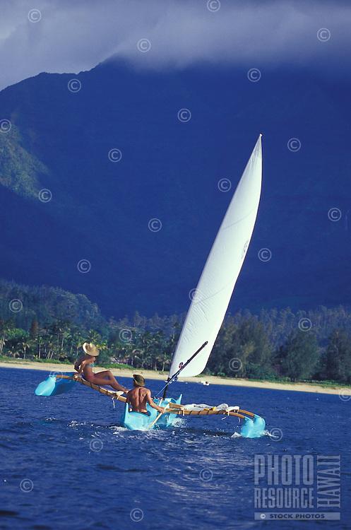 Couple sailing Hawaiian 'holopuni' outrigger canoe in tradewinds with Mount Waialeale in background, on Hanalei Bay, Kauai