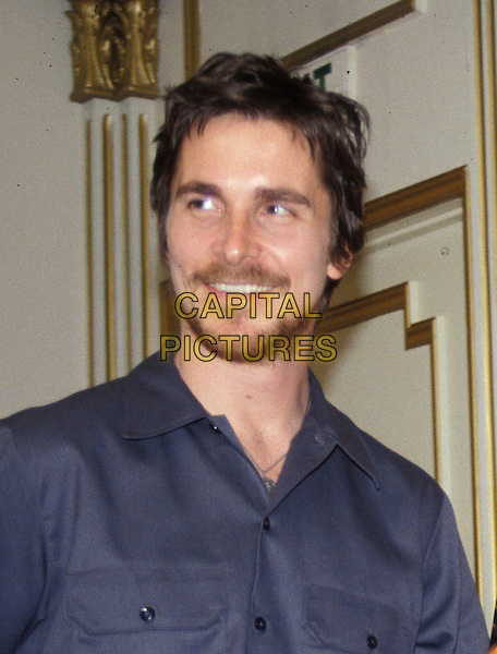 CHRISTIAN BALE.June 2005.half length facial hair mustache goatee blue shirt.www.capitalpictures.com.sales@capitalpictures.com.© Capital Pictures.