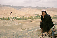 A young Taleban at the Bamiyan airport with the decapitate 34 meters Buddha statue on the left, in 1999. .The blow up was made with explosive behind the head causing the decapitation and collapse of all main fresco in the niche of the 34 meters Buddha..The Taleban started to seriously destroy the Bamiyan Buddha in autumn of 1999..These magnificent colossal statues, created during the 3rdâ4th centuries A.D., attracted pilgrims for centuries, far beyond the time when Buddhism languished in India following the disastrous visitation of the Hephthalite Huns in the 5th century, the subsequent resurgence of Hinduism, and the arrival of iconoclastic Islam in the 7th century..The entire niche was once covered with paintings dating from i he late 5th to the early 7th centuries.
