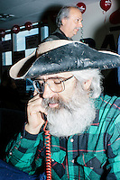 """Anthony Nino (green plaid), of Amherst, NH, calls potential voters from the phonebank at the campaign headquarters of Kentucky senator and Republican presidential candidate Rand Paul in Manchester, New Hampshire. At the time, Paul was visiting the office to greet supporters and call voters. Nino said his tricorne hat, which he made himself from a deer he hunted, was meant to """"give a visual message that our movement is based on the Constitution."""""""