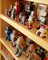 A fascinating collection of vintage toy robots is displayed on open shelving in the living area