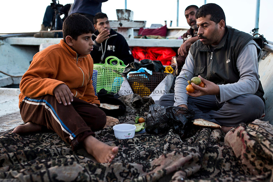 Gaza sea: Before starting fishing, the crew is having their dinner while the boat is navigating. <br /> <br /> Mer de Gaza: Avant de commencer &agrave; p&ecirc;cher, les p&ecirc;cheurs dinent pendant que le bateau navigue.