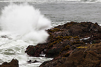 Spray flies from a wave crashing onto the rocky shoreline at Bean Hollow State Beach along the California coast.