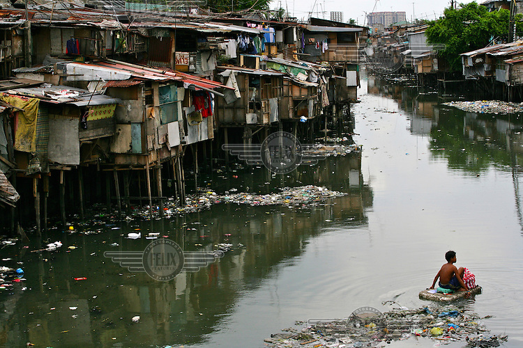 A boy, sitting on a polystyrene raft, floats past rubbish and slum housing lining a polluted canal in Metro Manila.