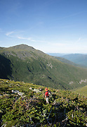 Hiker ascending the Six Husbands Trail during the summer months in the White Mountains, New Hampshire USA.
