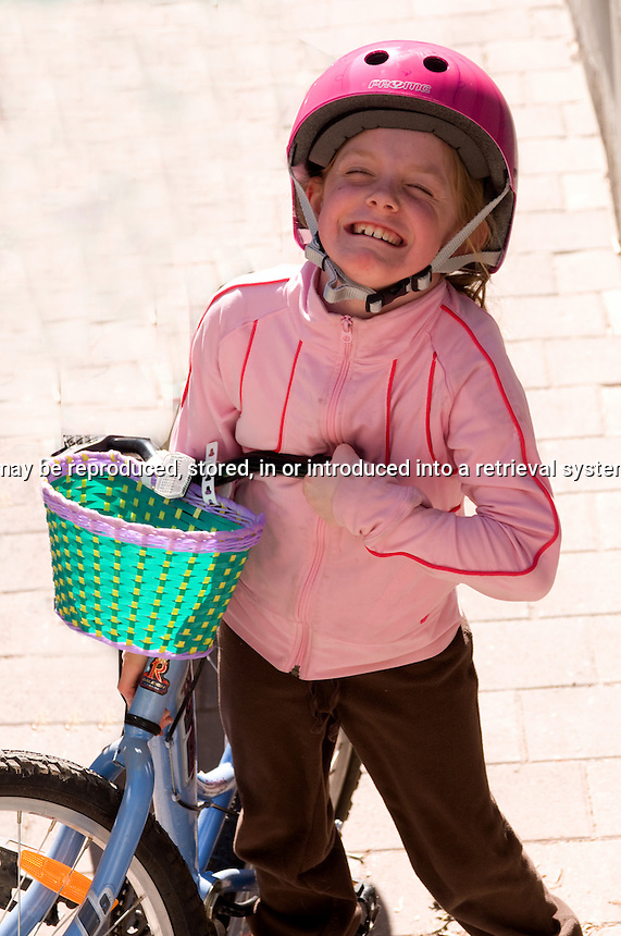 Young girl picking up her bike making a funny face