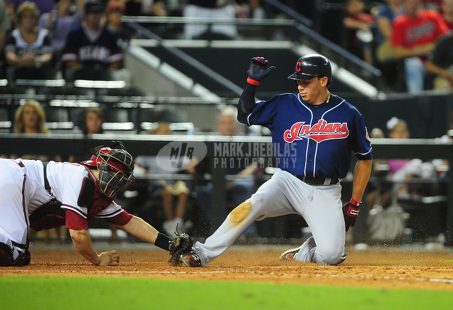 Jun. 27, 2011; Phoenix, AZ, USA; Cleveland Indians base runner Asdrubal Cabrera slides safely into home ahead of the tag by Arizona Diamondbacks catcher Miguel Montero in the sixth inning at Chase Field. Mandatory Credit: Mark J. Rebilas-