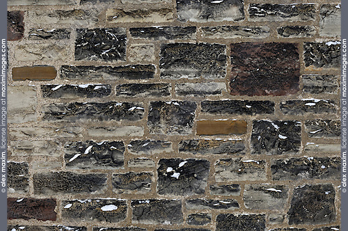 Old stone wall texture background with a bit of snow on it