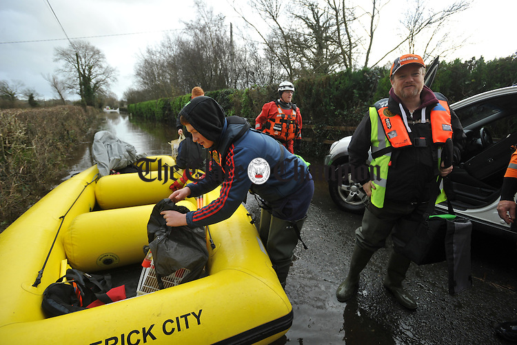 Mike Hogan and his sons Mark and Sean Hogan  collect their belongings after they were evacuated by boat from their home at Springfield Clonlara where they were cut of by the flood waters. Photograph by John Kelly.