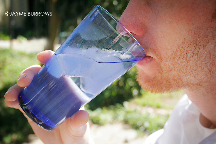 A young man drinks a cold glass of water on a warm afternoon.
