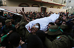 Relatives of Palestinian Ziyad Al-hawajri, react as mourners carry his body out of the family house during his funeral in Nuseirat, central Gaza Strip, Thursday, March 22, 2018. Al-hawajri, is one of the two members of Hamas security forces who were killed Thursday during an operation to arrest suspects wanted for a bombing that targeted the visiting Palestinian premier's convoy in Gaza last week. Photo by Ashraf Amra