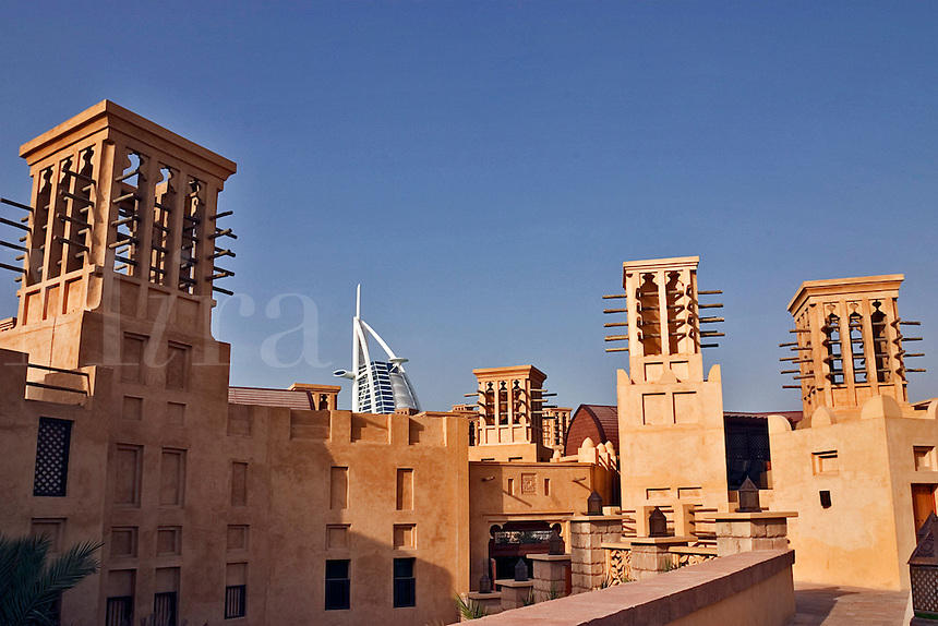 Dubai, United Arab Emirates. Madinat Jumeirah. Roof of souk with traditional wind towers of the region. Efficient form of forced draft air conditioning. Burj al Arab in background..