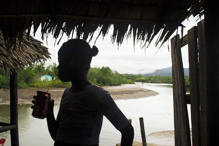 NUQUÍ, EL CHOCO, COLOMBIA -- DECEMBER 10:  A young girl sips on a Coke in riverside cafe in Nuqui on December 10, 2005. Nuquí is a small town on Colombia's isolated and untamed Pacific coast, an area sandwiched between endless miles of trackless rainforest and the Pacific Ocean. (Photo by Dennis Drenner/Aurora). ..