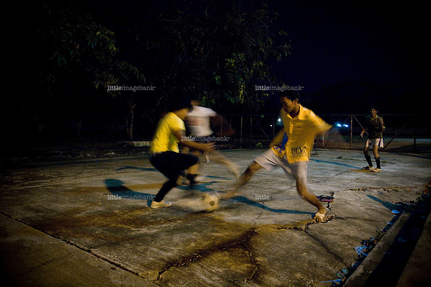 Youth playing football at night in the outskirts of Pattani city. Thailand is struggling to keep up appearances as the land of smiles has to face up to its troubled south. Since 2004 more than 3500 people have been killed and 4000 wounded in a war we never hear about. In the early hours of January 4th 2004 more than 50 armed men stormed a army weapons depot in Narathiwat taking assault rifles, machine guns, rocket launchers, pistols, rocket-propelled grenades and other ammunition. Arsonists simultaneously attacked 20 schools and three police posts elsewhere in Narathiwat. The raid marked the start of the deadliest period of armed conflict in the century-long insurgency. Despite some 30,000 Thai troops being deployed in the region, the shootings, grenade attacks and car bombings happen almost daily, with 90 per cent of those killed being civilians. 23.09.07. Photo: Christopher Olssøn