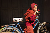 A very young apprentice monk in the Nang Yone Monastery near Hsipaw, Myanmar, has acquired a bicycle which is much too big for him, an Inter Milan knitted woollen hat and an ice-cream cone of a lurid pink colour.