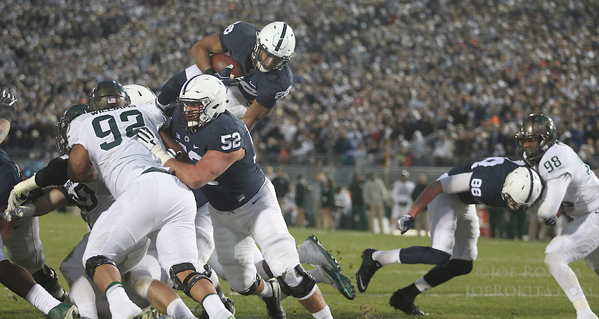 State College, PA - 11/26/2016:  Penn State RB Saquon Barkley (26) jumps over the top to score a touchdown. #7 Penn State defeated Michigan State by a score of 45-12 to secure the Big Ten conference East Division championship on Senior Day, Saturday, November 26, 2016, at Beaver Stadium in State College, PA.<br /> <br /> Photos by Joe Rokita / JoeRokita.com