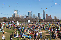 An army of colorful kites sway in the breeze at the Zilker Park Kite Festival, overlooking the downtown Austin Skyline on a beautiful Sunday afternoon.