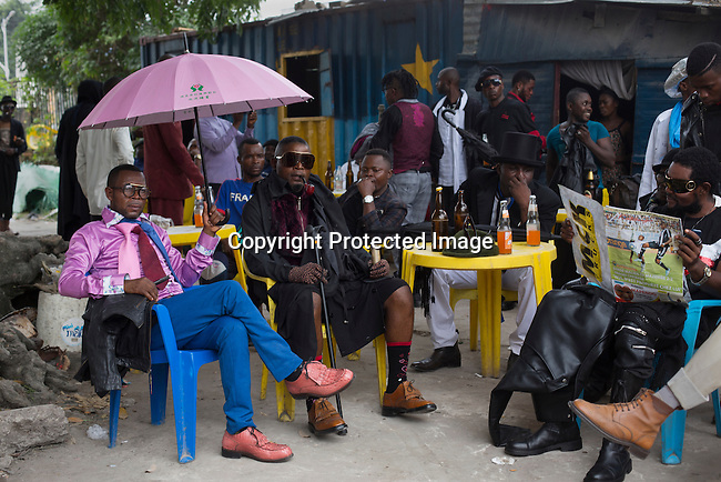 "KINSHASA, DEMOCRATIC REPUBLIC OF CONGO - FEBRUARY 10: Sapeurs take a break while paying their respect to Stervos Nyarcos, the founder of the .kitendi religion., which means clothing in local language Lingala. Nyarcos was known as the leader of the Sape movement, at Gombe cemetery on February 10, 2016 in Kinshasa, DRC. The word Sapeur comes from SAPE, a French acronym for Société des Ambianceurs et Persons Élégants. or .Society of Revellers and Elegant People. and it also means, .to dress with elegance and style"". Most of the young Sapeurs are unemployed, poor and live in harsh conditions in Kinshasa,  a city of about 10 million people. For many of them being a Sapeur means they can escape their daily struggles and dress like fashionable Europeans. Many hustle to build up their expensive collections. Most Sapeurs could never afford to visit Paris, and usually relatives send or bring clothes back to Kinshasa. (Photo by Per-Anders Pettersson)"