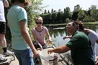 Vorsitzender Andreas Krüger vom ASV Rotauge kontrolliert die Reuse, Ilonka Ludwig, Laura und Daniela Schätzke sehen zu